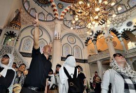 無料見学会の参加者に礼拝堂の説明をする下山茂さん。「礼拝では(両手を下から耳の横まで上げる)最初のポーズで仕事のこととか、家のこととか、全部後ろへやって、神と向き合う。イスラムは形の宗教」=8月13日、東京都渋谷区の東京ジャーミイ(撮影・萩原達也)