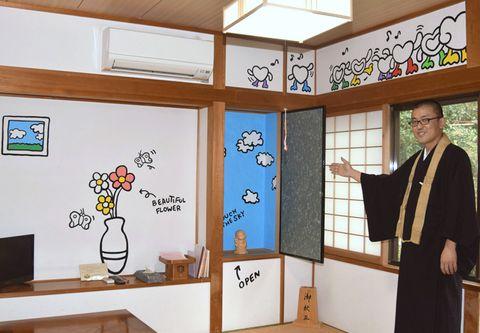 壁一面が作品で埋め尽くされた岩本寺宿坊の一室と窪博正住職(四万十町茂串町)