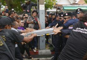 22日、バンコクのタマサート大周辺の道路で、警官隊(右側)が設置した鉄柵を取り去ろうとするデモ隊(共同)