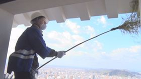 ササぼうきで松山城天守最上階の軒下のほこりを落とす参加者