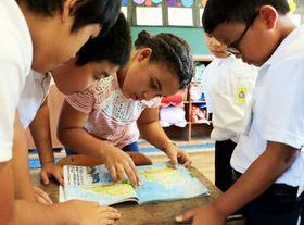 地図帳を見て自分の出身地を児童に説明するヨライオスさん(中央)