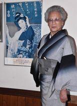 「〆丸」こと橋本シメ子さんと、18歳当時に撮影されたポスター=おいらせ町・桃川のおいらっせ交流館内