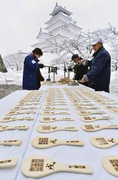 一枚一枚丁寧に進められる「飯べら」の焼き印押し作業=13日午前、会津若松市・鶴ケ城