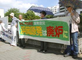 中部電力の株主総会会場前で、浜岡原発の廃炉を訴える人たち=26日午前、名古屋市