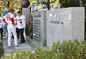 増設されたプロ野球広島の優勝記念碑(手前)。左端は緒方孝市監督=24日午前、広島市