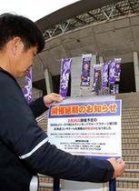 エディオンスタジアム広島の正面に26日の札幌戦の延期を伝える張り紙をするクラブ職員