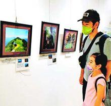 中四国の国立公園の魅力を紹介する展示に見入る来場者=徳島市立図書館
