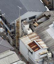 煙突が折れ、建物の屋根を突き破った現場=18日午後0時57分、大阪府枚方市