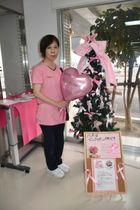 乳がん啓発のピンクリボンで飾ったツリーを、職場仲間と協力し勤務先の病院外来受付に展示している楠見かおりさん