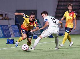 第1節以来の先発で、金沢の選手をかわしてドリブルする新垣貴之選手(左)