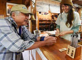 安全登山を願う木札を受け取る常念小屋の宿泊客(左)
