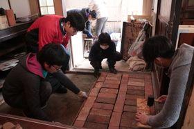 玄関の改修作業を進める市民団体「つくる」メンバーら=2月17日、長崎市浪の平町