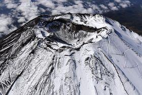 山梨県富士吉田市が「初雪化粧」を宣言した富士山の山頂=23日午後(共同通信社ヘリから)