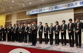 報告会であいさつする岡山シーガルズの河本昭義監督(中央)=岡山市内