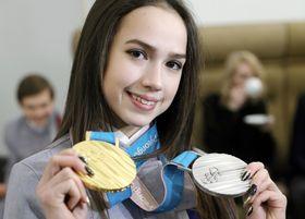 モスクワの大統領府での勲章授与の式典を前に、平昌冬季五輪で獲得した金、銀メダルを見せるザギトワ選手=2月28日(タス=共同)