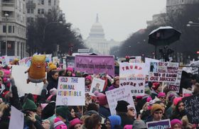 米連邦議会議事堂(奥)周辺で行われた「女性大行進」で、トランプ政権に抗議する市民ら=19日、ワシントン(共同)