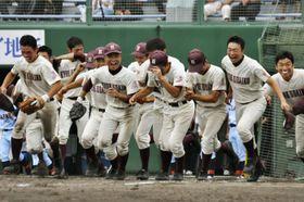 第100回全国高校野球選手権大会への代表一番乗りを決め、駆けだす旭川大高の選手たち=21日、北海道旭川市