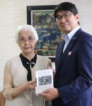 田上市長に「ナガサキ」を手渡した岡田さん(左)=長崎市役所