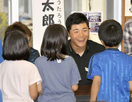 児童養護施設を訪問し、子どもたちと笑顔で話す日本ハム・清宮=20日、沖縄県名護市