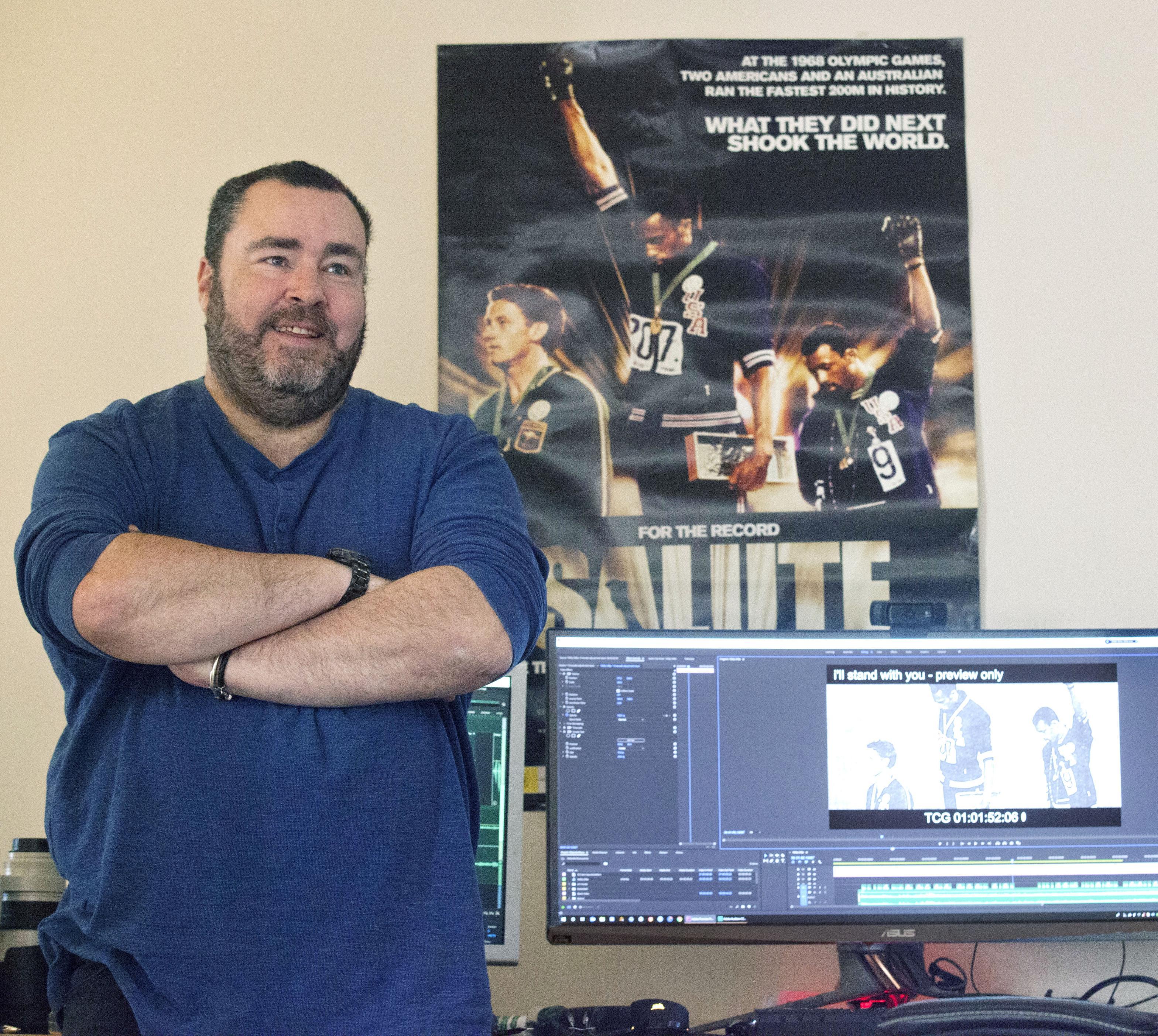 映画「SALUTE」の監督マット・ノーマン。映画ポスターはメキシコ五輪男子200メートル表彰式の場面で(左から)伯父のピーター・ノーマン、トミー・スミス、ジョン・カルロス=9月、オーストラリア・ビクトリア州(共同)