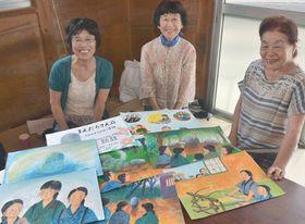 仲間と紙芝居を囲んで笑顔を見せる西山芳枝さん(左)