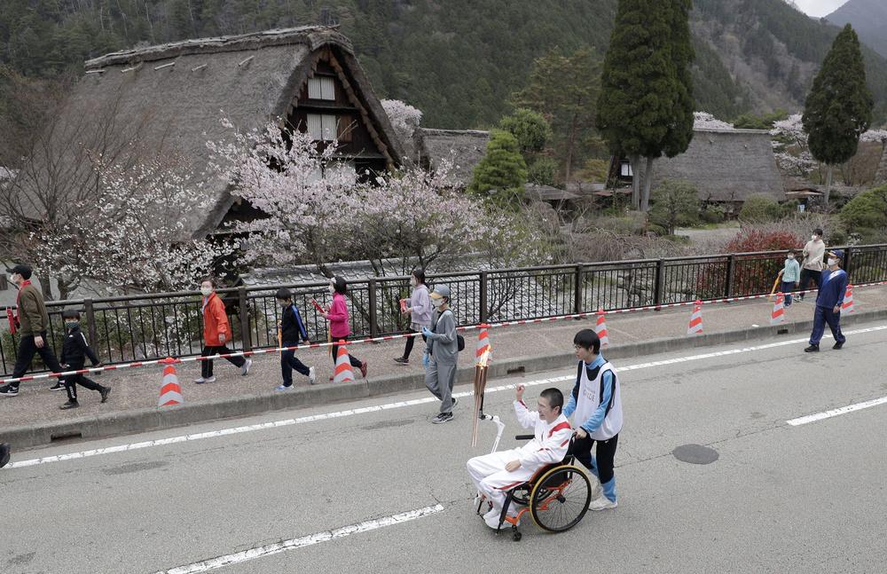 下呂温泉合掌村の前を行く聖火ランナー=4日午前、岐阜県下呂市