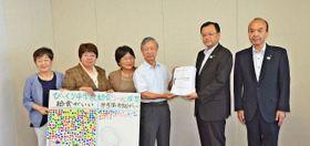 市立中学校での完全給食の実現を求め、落合市長(右から2人目)に署名を手渡す市民団体のメンバー=平塚市役所
