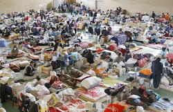東日本大震災の被災者で混雑する中学校の避難所=2011年3月、岩手県陸前高田市