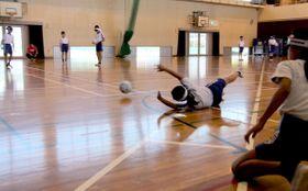ゴールボール体験で、ゴールを防ごうと必死に体を張ってボールを止めようとする児童=三豊市三野町、下高瀬小