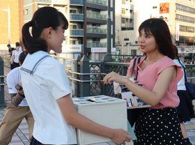募金活動をする高校生(左)=JR長崎駅前高架広場
