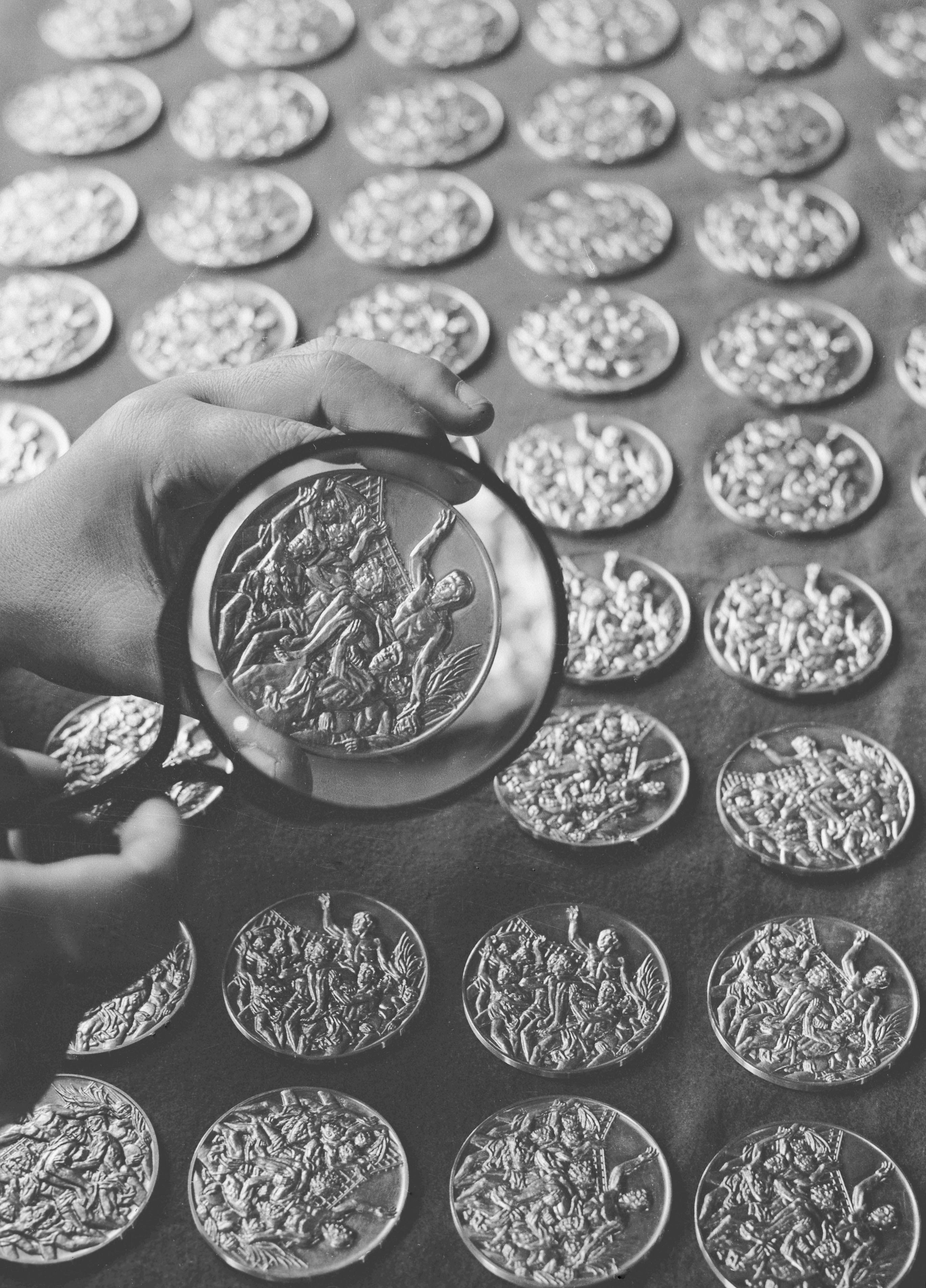 1964年6月、大阪市の造幣局でつくられ検査を受ける東京五輪の金メダル