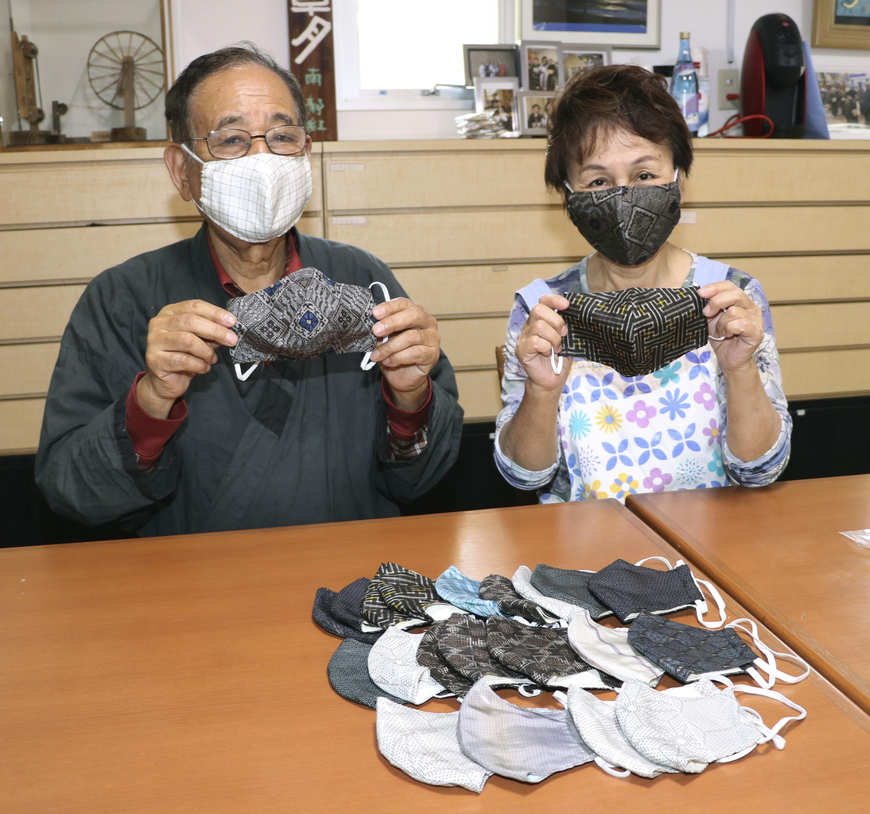 大島紬の生地で作ったマスクを手にする、夢おりの郷の南祐和会長(左)=17日、鹿児島県龍郷町