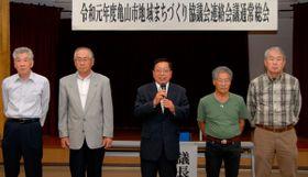 【本年度の抱負を述べる鈴木会長(中央)と新役員ら=亀山市若山町の市社会福祉センターで】