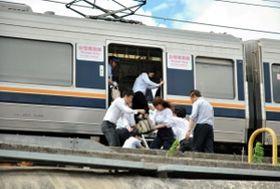 JR西日本の職員に支えられ、はしごを使って電車を降りる乗客=18日午前10時14分、西宮市六湛寺町