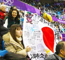 宮原知子選手への応援メッセージが書かれた国旗を手に声援を送る観客(21日、江陵)
