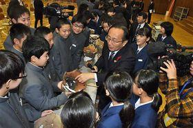 三村知事(写真中央)の説明を受けながら、縄文土器に触れる三内中の生徒たち