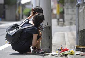 船戸結愛ちゃんが虐待を受け、亡くなった自宅アパートに花を手向けに来た親子=6月、東京都目黒区