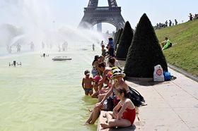 エッフェル塔を望むトロカデロ庭園の池で涼む人々=7月26日、パリ(ゲッティ=共同)
