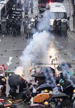 デモ隊の若者ら(手前)に向けて催涙弾を発射する警官隊=25日、香港・新界地区(共同)