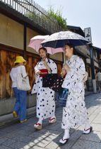 厳しい暑さが続く中、京都・祇園で日傘を差して歩く女性=19日午前