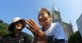 「ほんと、ありがたかねぇ」と崎津教会の前で手を合わせるはるのちゃん(右)=熊本県天草市河浦町