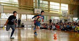 ドリブルする安在和樹選手と競走する児童=唐津市の長松小