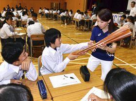 2020年東京五輪・パラリンピックの聖火リレーの意義を学ぶ特別授業で、トーチを手に取る渡波中学校の生徒。右は元五輪マラソン選手の千葉真子さん=27日午後、宮城県石巻市