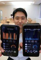 いびきの激しさを表すスマートフォンアプリの画面を見せる谷川記者。左がいびき音が大きい手術前