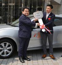 アクセラの前で下野さん(左)にキーの模型を手渡す松田会長