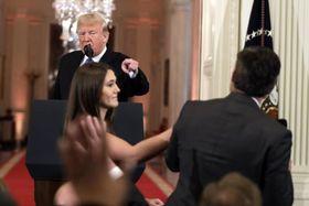 7日、米ホワイトハウスでのトランプ大統領の記者会見で、CNN記者(右)のマイクを取ろうとするスタッフ(AP=共同)