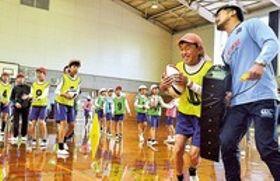 中園真司選手(右)とタックルの練習体験をする児童=17日午前、掛川市立西郷小