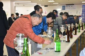 徳島県三好市で開かれた「四国酒まつり」で地酒の試飲を楽しむ人たち=24日午前