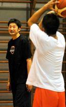 自主練習する選手を見守る堀田新監督(左)