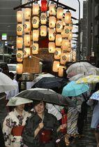 京都・祇園祭が「宵々々山」を迎え、雨の中に並ぶちょうちんの明かりに照らされた山鉾=14日